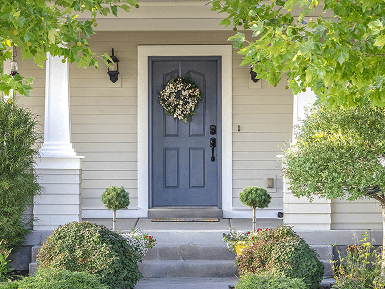 straight-on view of a home's gorgeous portico with a stunning blue painted front door and spring-time wreath