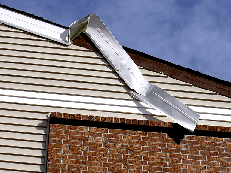 close up view of damaged home exterior siding under roof